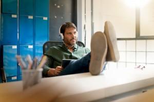 man-wearing-headphones-working-in-modern-office-with-feet-up-on-desk_69315-730